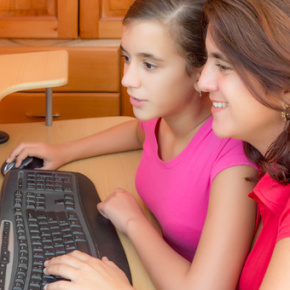 Hispanic girl and her mother working on a computer