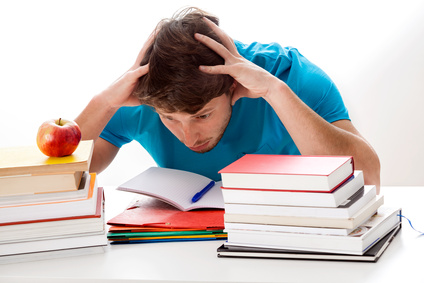 Overwhelmed teen with ADHD looking at a large stack of books and a notebook while holding his hands to his head in distress