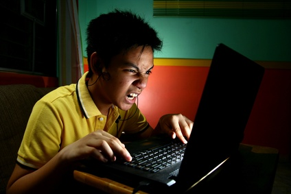 Teen with ADHD looking confused as he plays on the computer at night