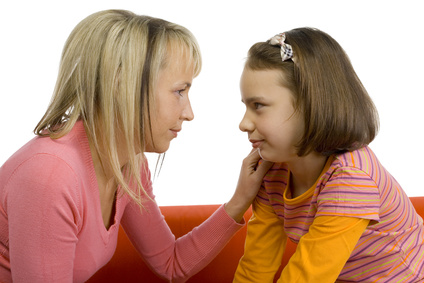 A side view of a neurodiverse mom looking compassionately at her neurodiverse child in the eye and resting her hand on her shoulder.