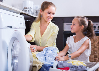 mom and daughter with bin near washing machine