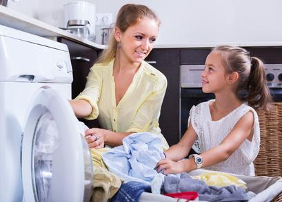 mom and daughter with bin near washing machine