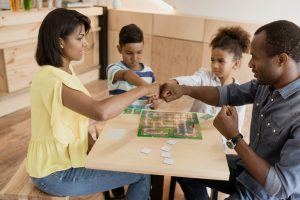 family playing board game in cafe