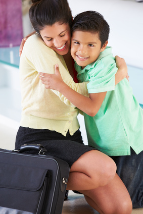 Mother bending down at her child's level to happily hug her son with ADHD who is also smiling with joy
