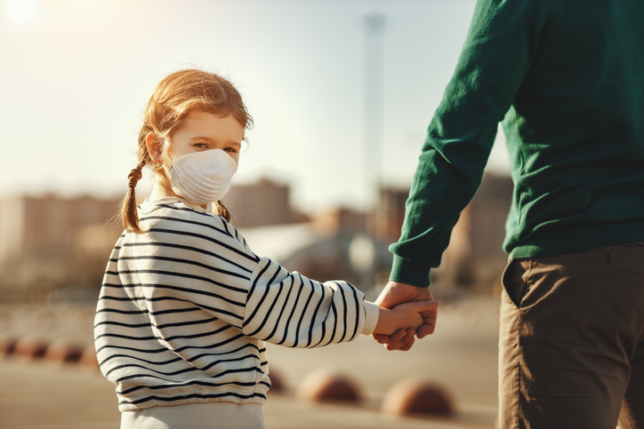 A young girl child with ADHD with a mask on and pigtail braids walking and holding her fathers hand who is practicing parent self-care by going out in town