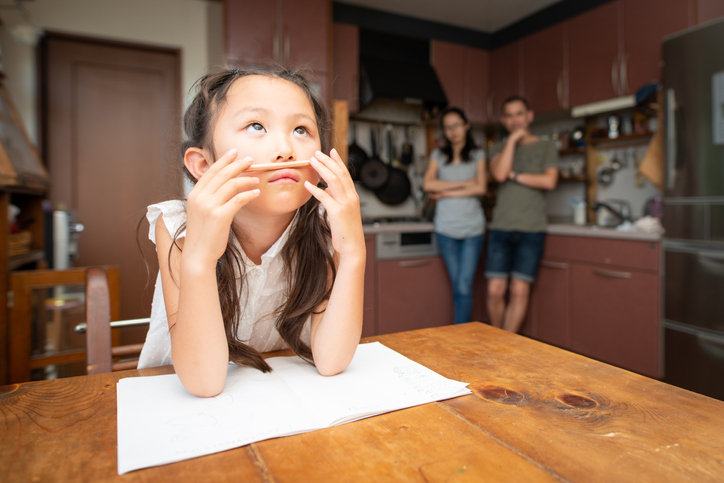 Young girl with ADHD and motivation issues playing with a pencil on her face instead of doing homework at the kitchen table with her parents watching in the background