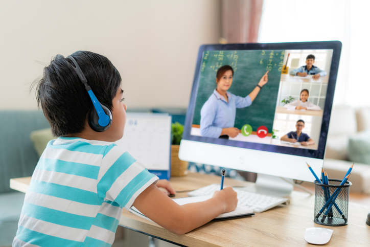 Child with ADHD with headphones on engaged in online learning at home.