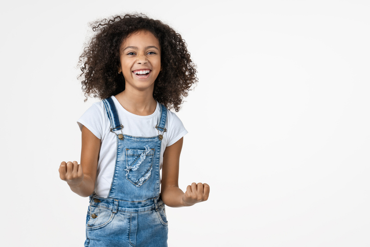 Happy kids with ADHD showing an exciting, accomplished gesture with her arms
