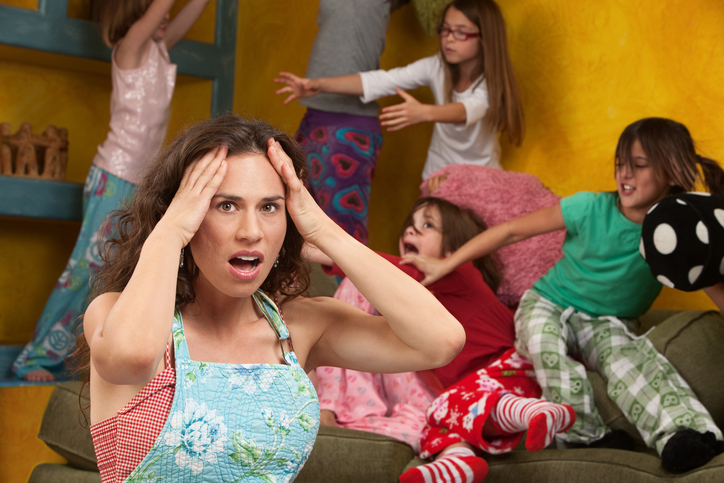 Mother parenting kids with ADHD experiencing pandemic burnout and resilience fatigue looking distressed as they 5 kids play behind her