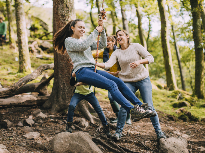 Mother playing with her teens with ADHD out in nature on a swing to relieve stress from pandemic burnout