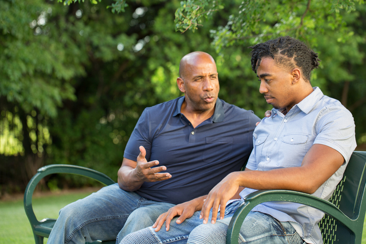 Father having a supportive conversation his teenage son with ADHD on a bench at a park