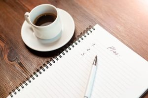 A notebook on a table next to coffee with the blank outline for a plan on it