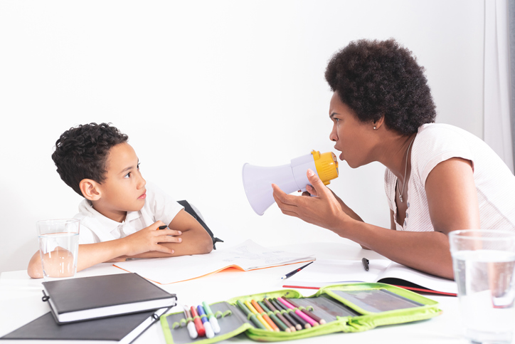 Mother at the table helping her son with ADHD do homework while speaking into a microphone too close to him as he backs away.