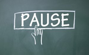 A chalkboard illustration of a hand pressing the word PAUSE that's drawn as a button.