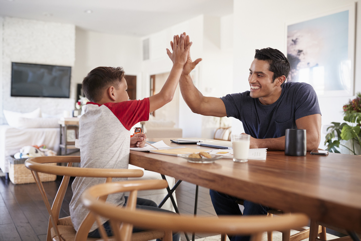Happy father high-fiving his young son with perfectionism and ADHD at the kitchen table, applauding progress over perfection