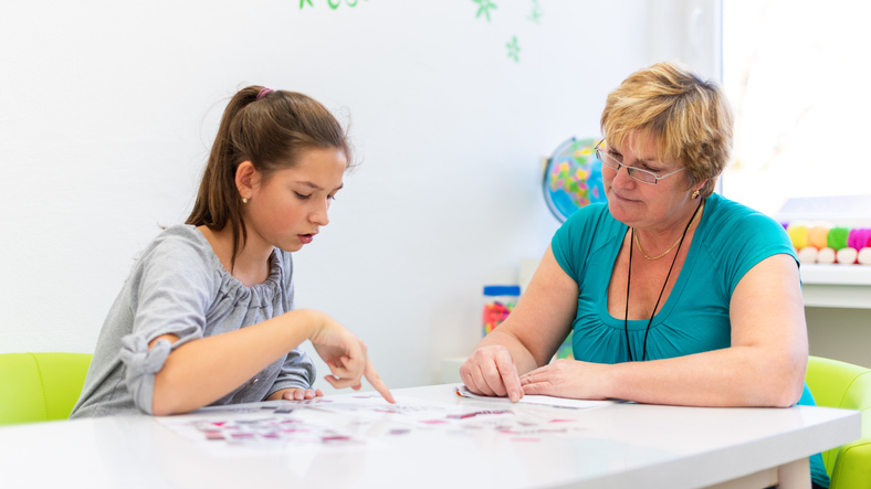 Teacher helping a neurodiverse girl with ADHD do school work in the classroom