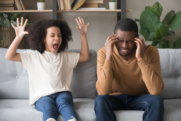 Father holding his hands to his temple in distress while his daughter with ADHD is screaming next to him on the couch with her hands in the air