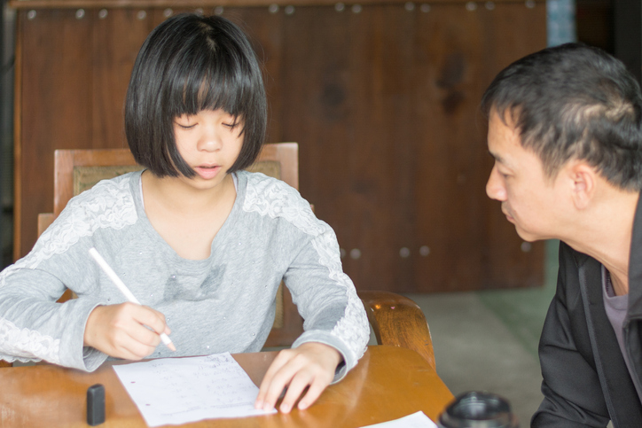 Father helping his daughter with ADHD doing her homework at the kitchen table