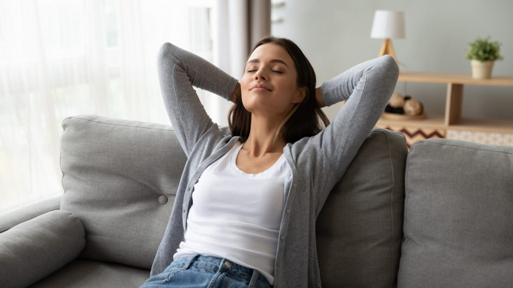 Parent enjoying a moment of relaxation leaning back on the couch with her eyes closed after spring cleaning and decluttering