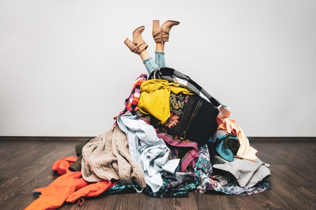 Teen girl with ADHD stuck upside down in a huge pile of clothes that's a mess before spring cleaning