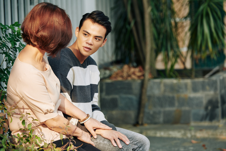Teen boy with ADHD sitting on a bench and having a serious conversation his mother