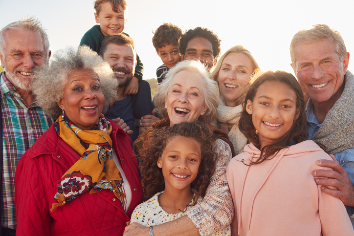 A big, happy neurodiverse family picture of multiple generations hugging outside in the sunlight and looking at the camera