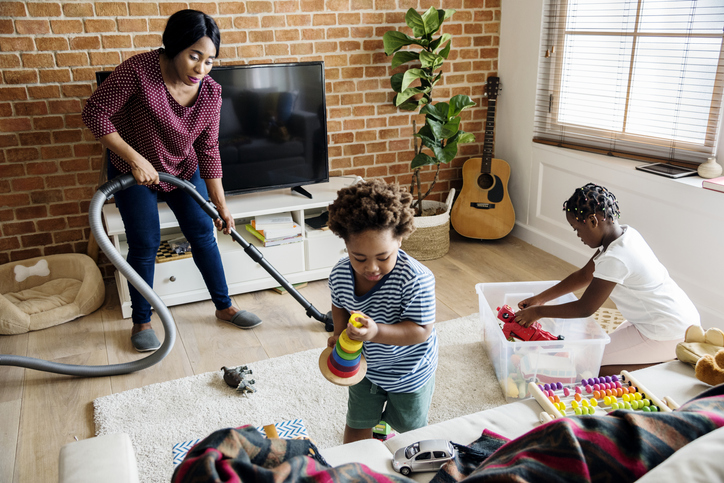 Mother spring cleaning and decluttering the living room with her ADHD kids
