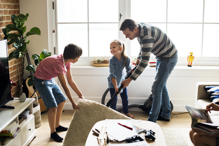 Father with his two kids with ADHD vacuuming under the rug for spring cleaning