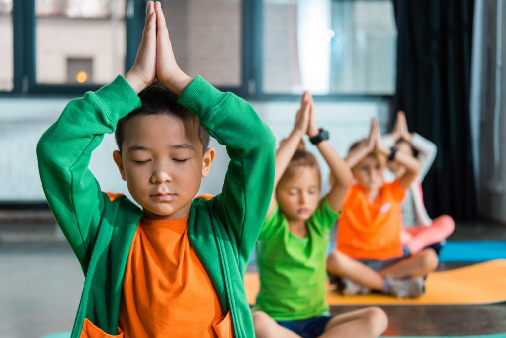 Boy with eyes closed with his hands together above his head in a yoga class with other kids to calm ADHD in boys and girls