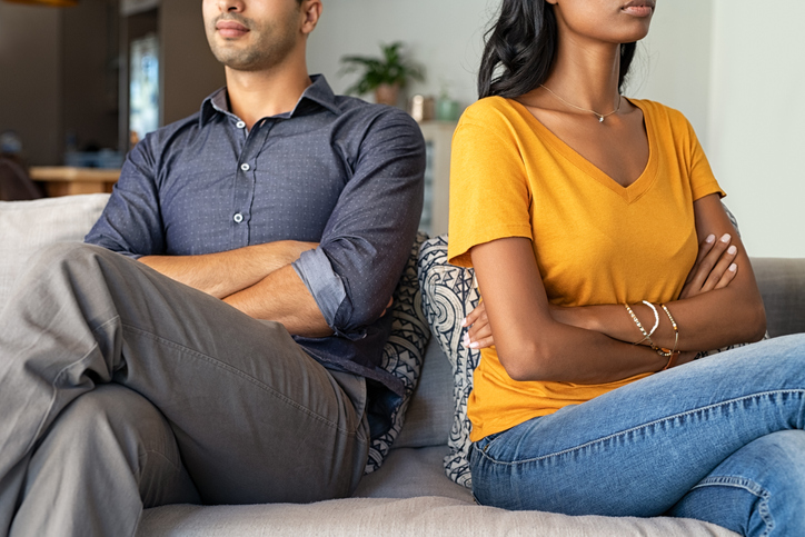 Two parents in a disagreement with their arms crossed and looking away while sitting next to each other on a couch