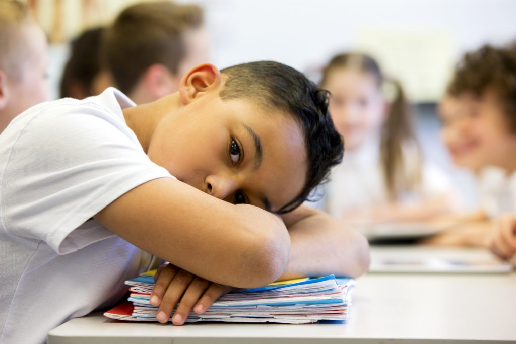 Boy with ADHD resting his head on a pile of brightly colored folders at school and looking at the camera