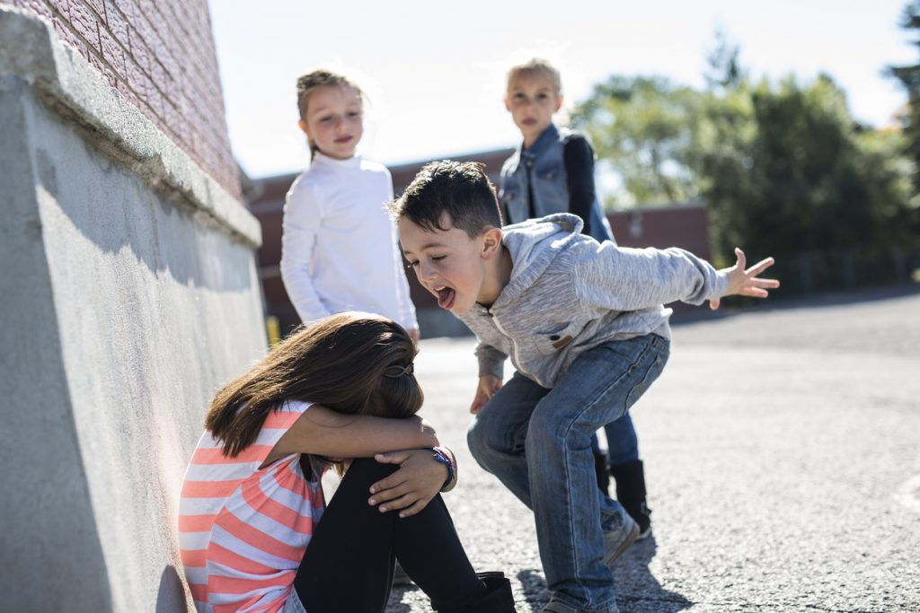 A young boy at recess teasing a girl, showing a social and emotional challenge for ADHD in boys, who is on the ground with her head down on her knees while two other kids watch in the background