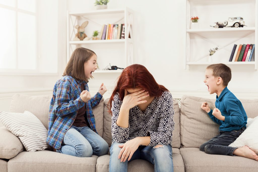 Stressed mother with her down and her hand over her face as her children are angry at each other sitting on either side of her