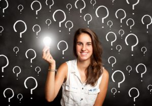 A neurodiverse teen girl holding a lit lightbulb in-front of a black background that has big white question marks all over it.