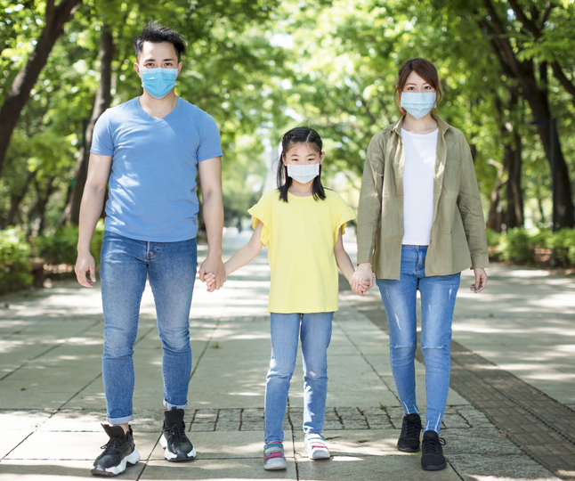 Parents holding their daughter's hand outside at the park together with masks on in post-pandemic world.