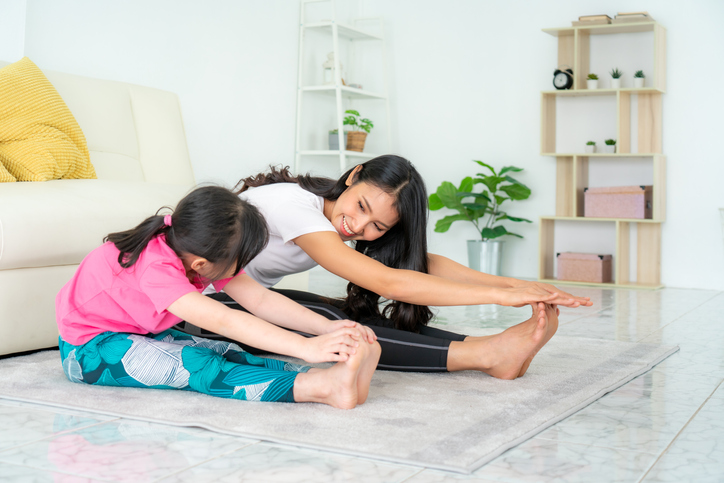 Mom with ADHD with her neurodiverse daughter stretching next to each other, touching their toes and looking at each other on the living room floor