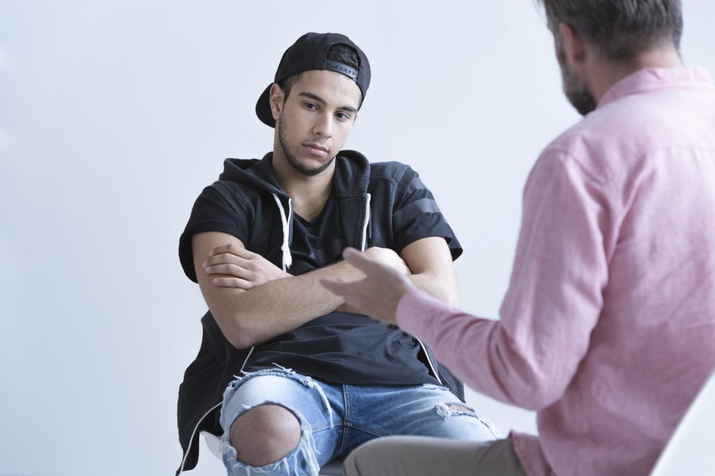 Teen boy with ADHD and rejection sensitivity dysphoria, sitting on a chair, looking down to the side with his arms crossed, unhappy, while his teacher speaks to him.