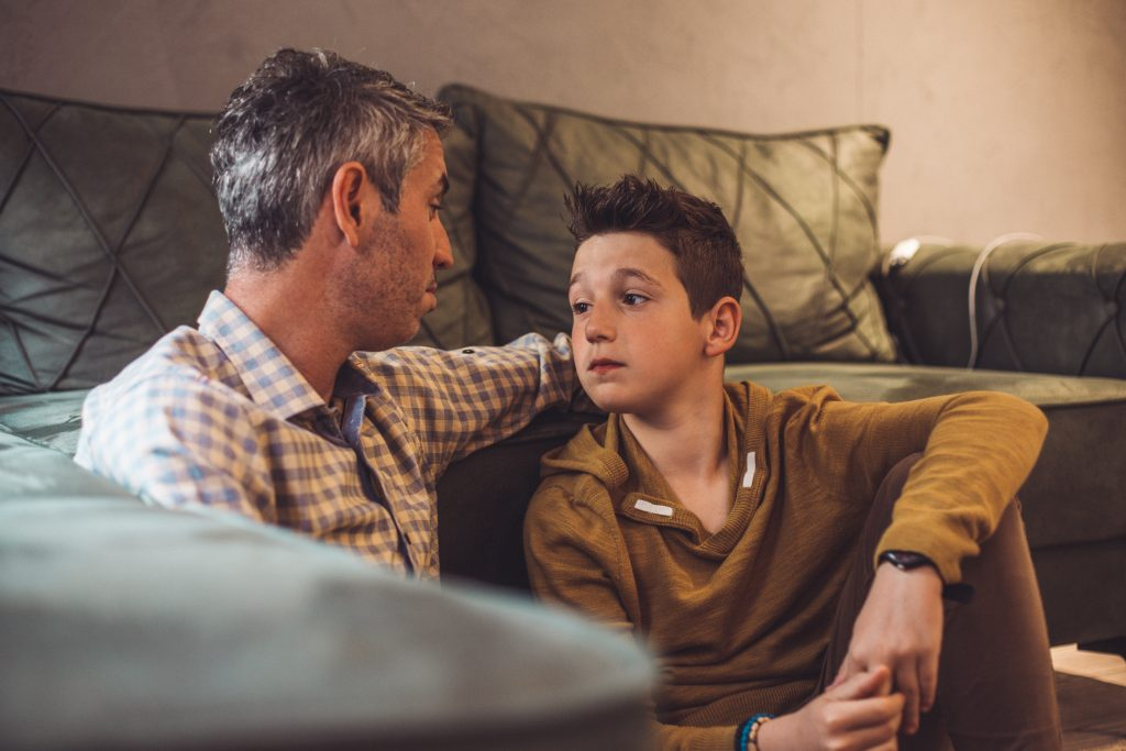 Dad with ADHD sitting on the floor in front of the couch with his son having an emotional conversation