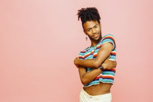 Gender-diverse young adult with ADHD wearing a blue and red striped shirt smiling and wrapping their arms lovingly around themself in front of a pink background