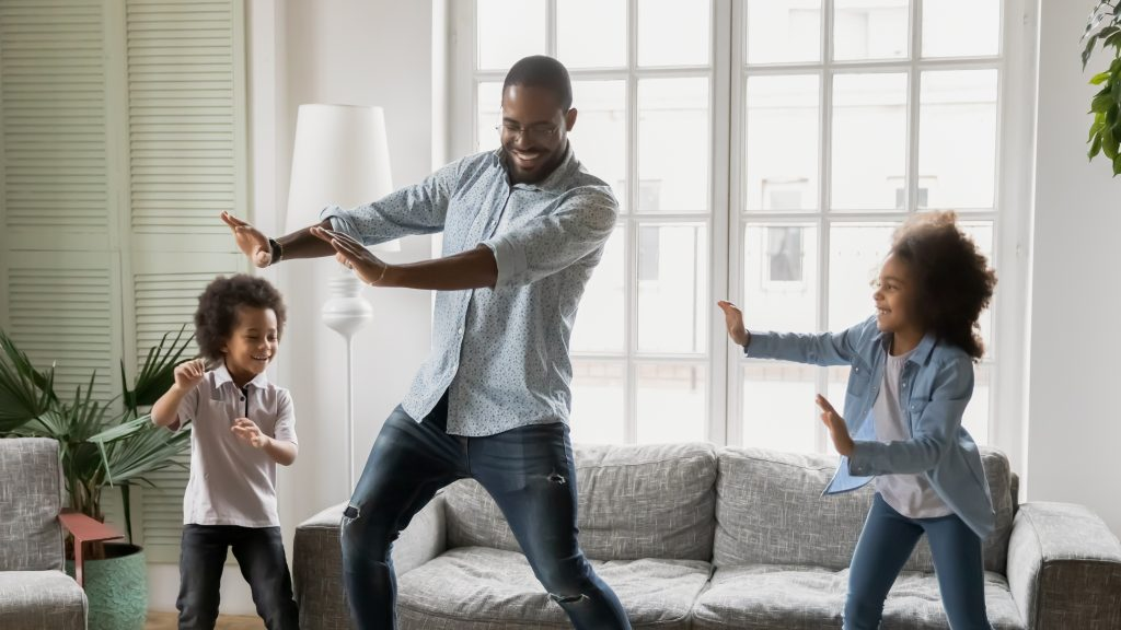 Dad with ADHD and his two daughters practicing a dance in the living room and smiling