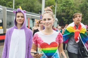 Three neurodiverse teens walking in a parade smiling and wearing LGBTQ pride clothing, a pride flag and unicorn onesie
