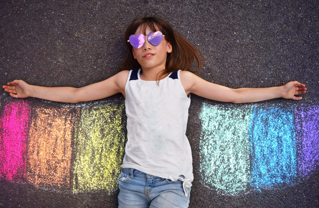 Neurodiverse child with purple heart-shaped sunglasses laying on pavement with rainbow pride flag stripes beneath their arms like wings