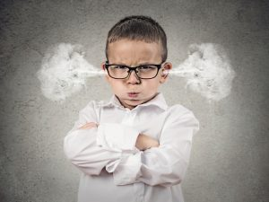 Child with ADHD feeling anger with his arms crossed and smoke coming from his ears