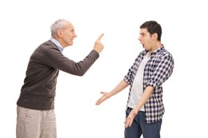 Grandfather angrily pointing his finger at a surprised and defensive teen boy