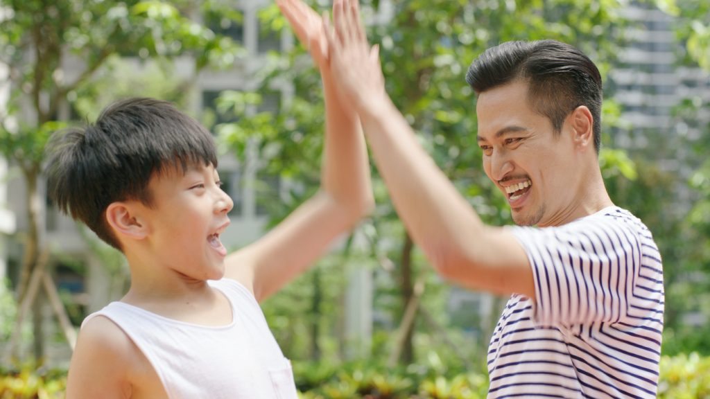 A father high-fives his young, neurodiverse, adolescent son, both smiling