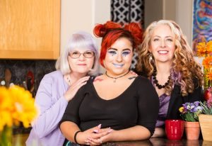ADHD teen with red hair and blue makeup smiling with mother and grandmother in the kitchen