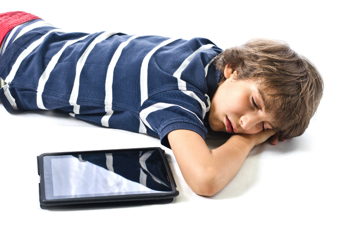 Teenage boy with ADHD with shaggy brown hair wearing a blue and white striped shirt lying on the white ground next to his tablet.