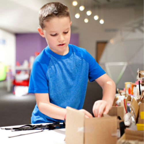Young boy with ADHD in a bright blue shirt taping together cardboard in a craft project next to a bunch of craft supplies in a large art room.