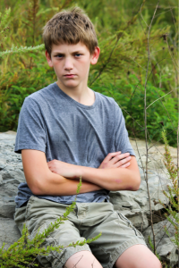 Boy with ADHD sitting outside on a rock looking upset with his arms crossed and looking at the camera