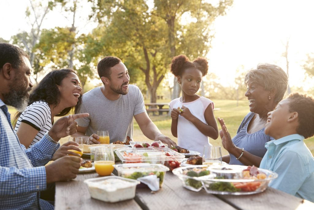 Multigenerational family of 6 eating and sitting at a picnic table outside during a bright sunset